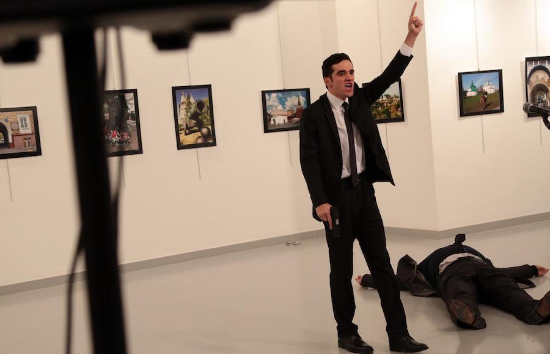A man gestures near to the body of Ambassador Karlov at a photo gallery in Ankara, Turkey, Dec. 19, 2016. Burhan Ozbilici / AP