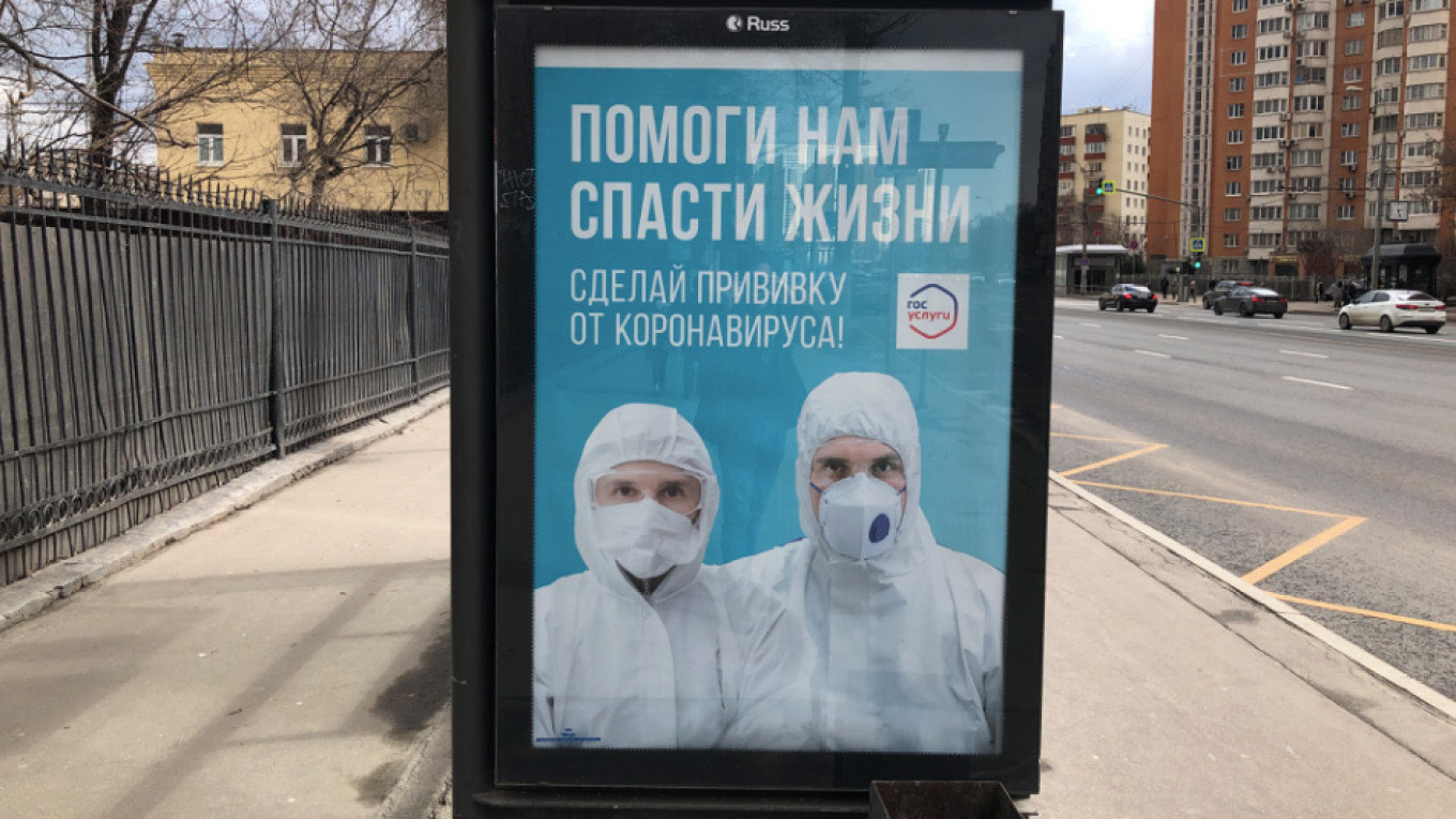 """Russia's vaccination campaign has started slowly. A poster encouraging people to be vaccinated reads """"Help us save lives."""" Felix Light / MT"""