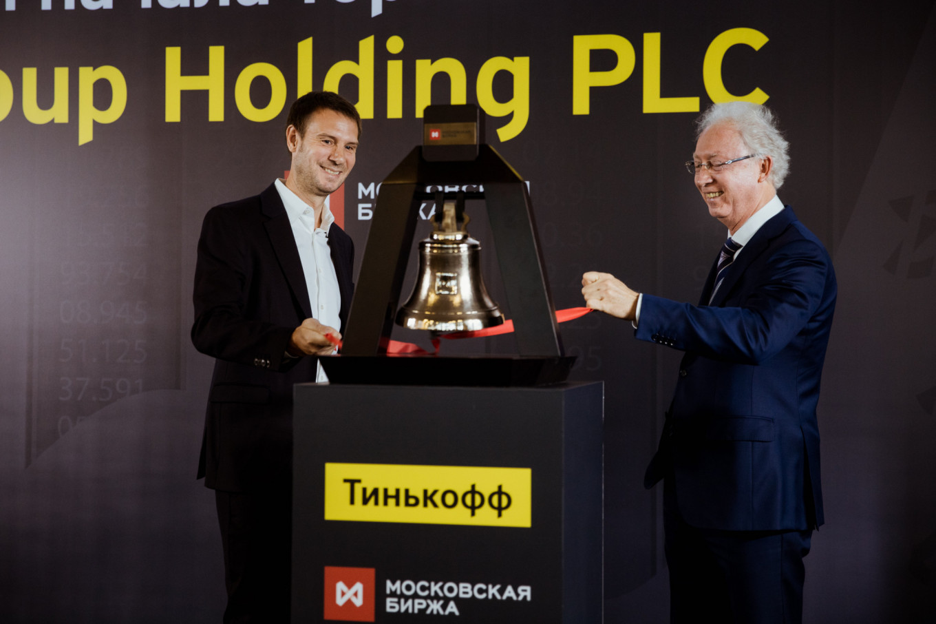 Tinkoff CEO Oliver Hughes and Oleg Vyugin of the Moscow Exchange ring the stock market's opening bell at a ceremony to mark the launch of Tinkoff's secondary listing.				 				Tinkoff Bank Media