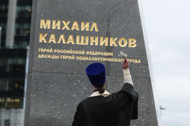 A Russian Orthodox priest sprinkles holy water on the new statue of Mikhail Kalashnikov. Kirill Zykov / Moskva News Agency