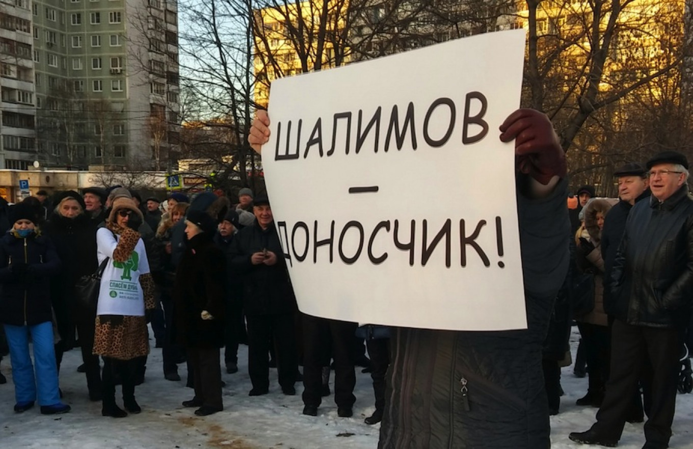 Protesters gather in the park in northern Moscow and one protester holds a placard describing local priest Oleg Shalimov as a 'snitch.' Eva Hartog / MT