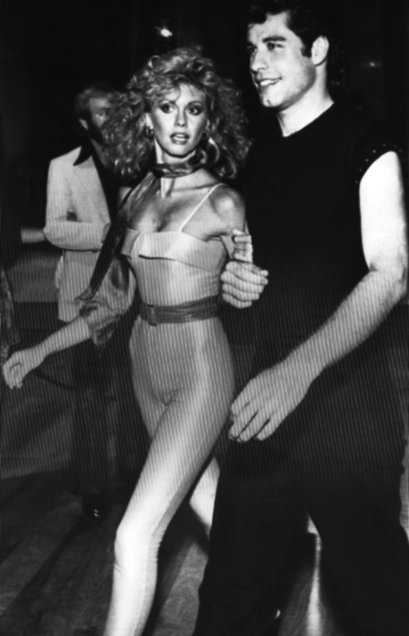 """Olivia Newton-John and John Travolta walk through the crowd of guests at a party following the premiere of """"Grease"""" in Los Angeles on June 5, 1978.  associated press"""