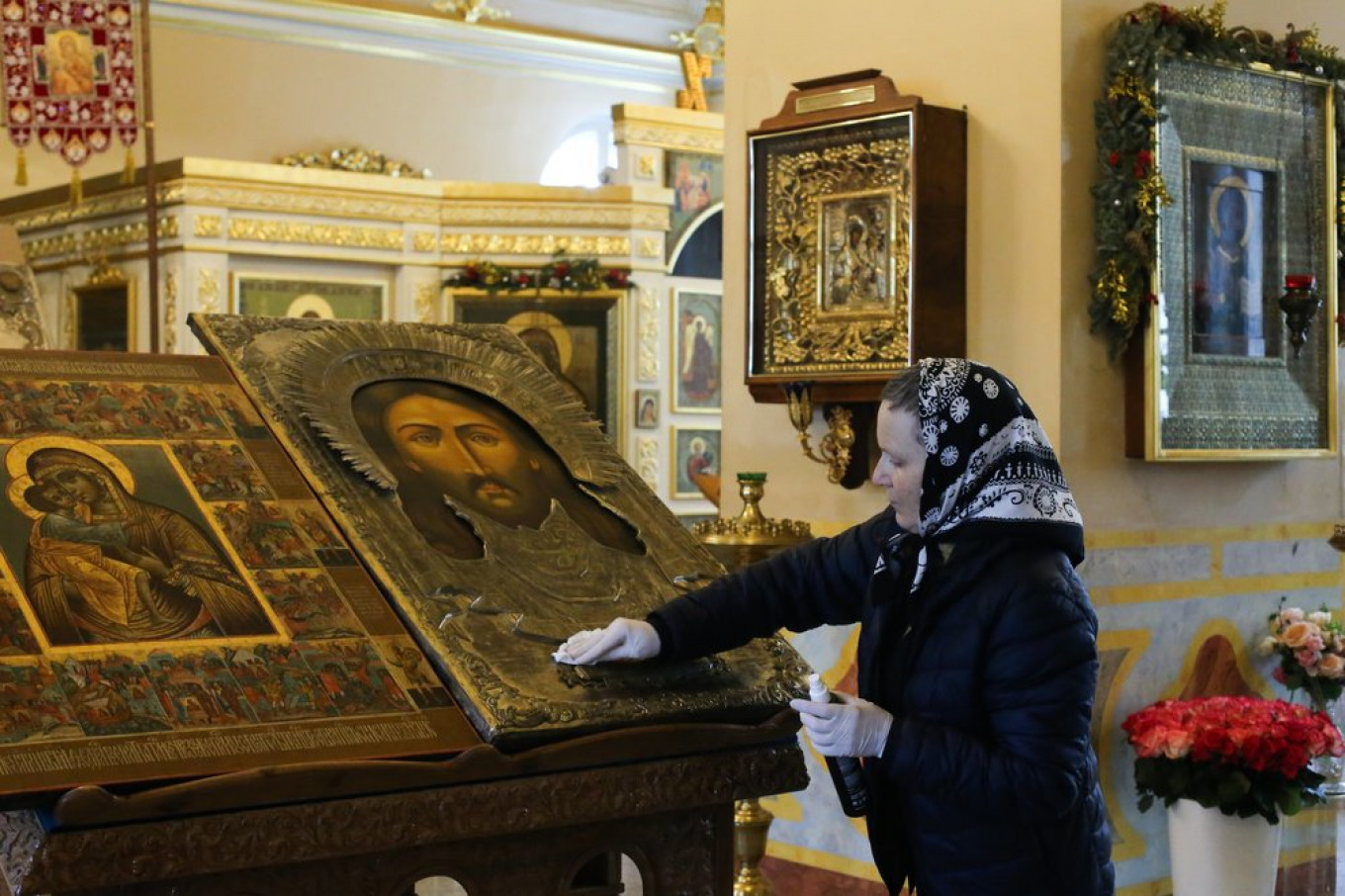 A worker disinfects an icon with an alcohol solution in the Church of St. Alexis in Rogozhskaya Sloboda. Sergei Vedyashkin / Moskva News Agency