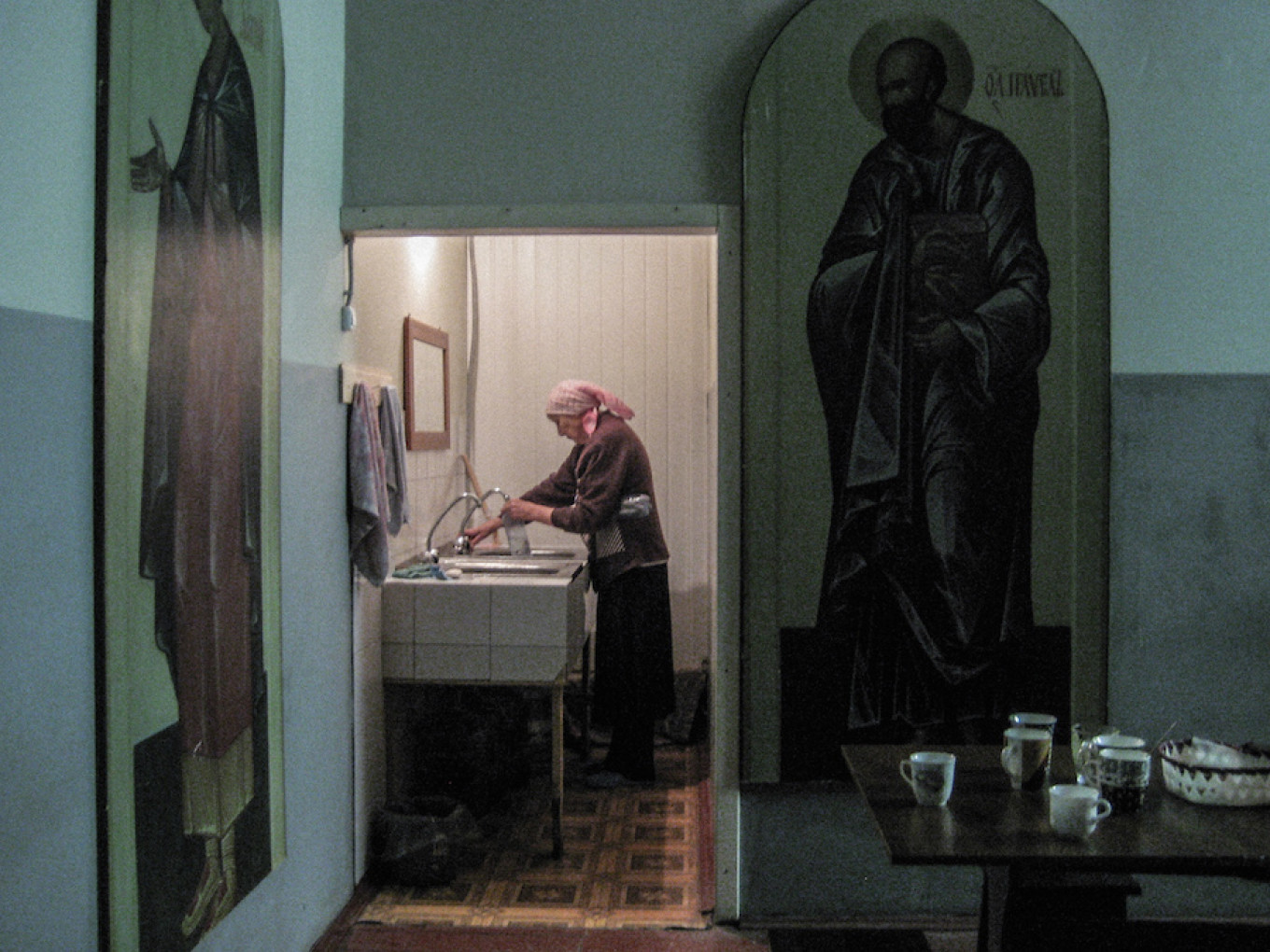 A pilgrim is filling the  bottle with water ready to be blessed by the priest. Diana Khachatryan