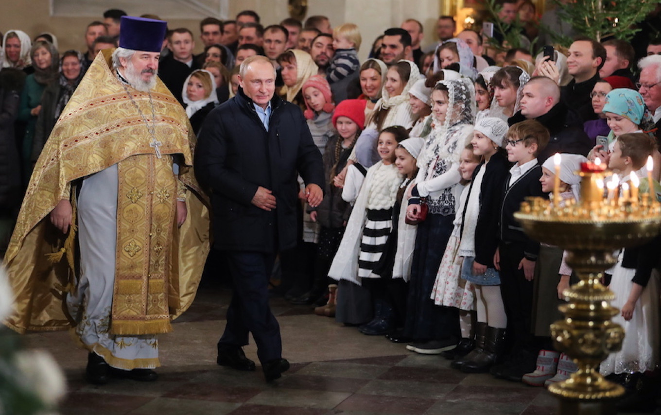 Putin walks past worshipers in Transfiguration Cathedral during the Christmas mass in St. Petersburg.				 				Alexander Demianchuk / TASS
