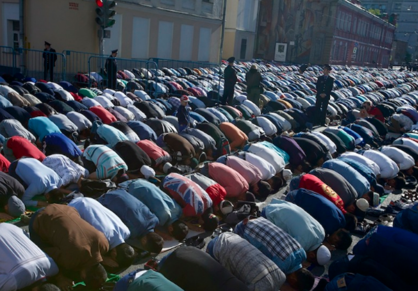 Police officers guard Muslims performing Eid al-Fitr prayers outside Moscow's Cathedral Mosque.  Ivan Sekretarev / AP