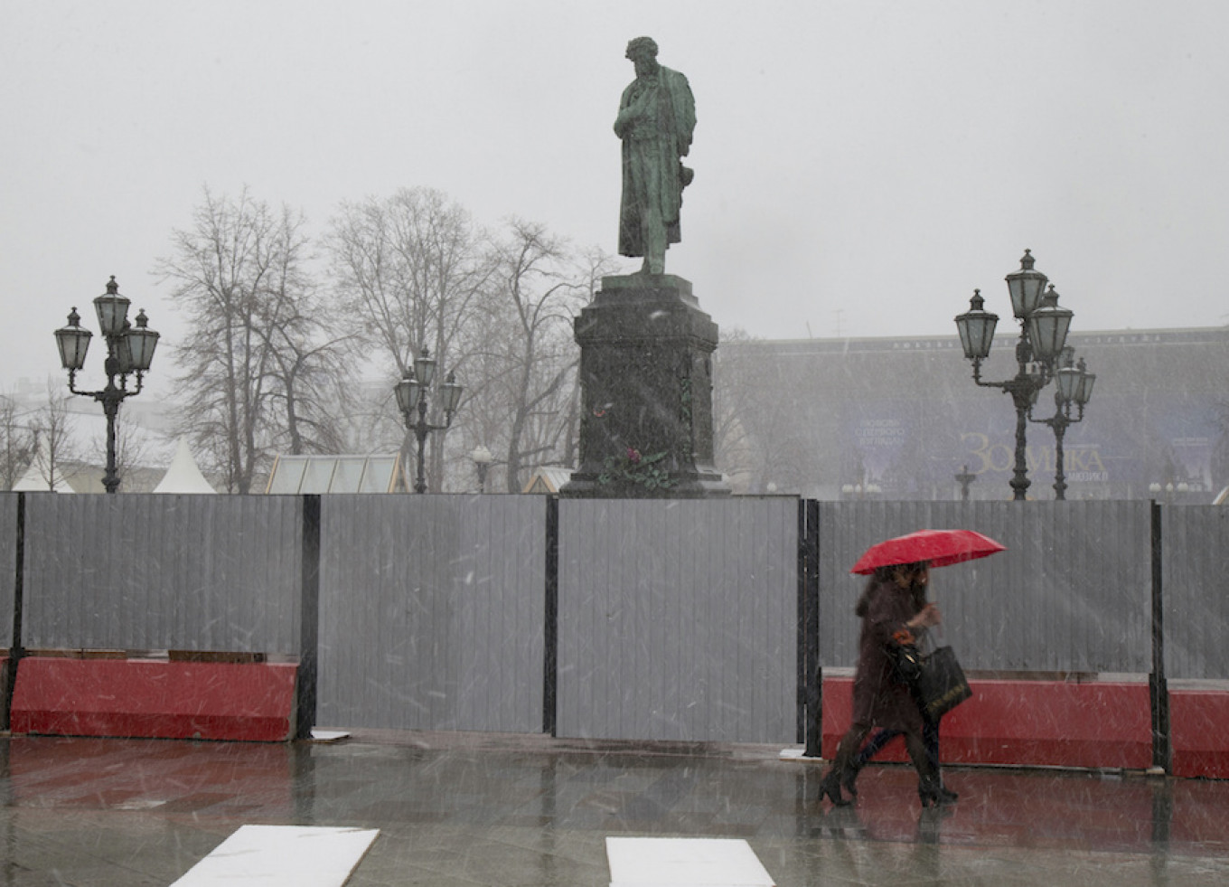 Women walk past the Alexander Pushkin monument surrounded by a barricade as it snows, in Moscow, March 28, 2017. 				 				Alexander Zemlianichenko / AP