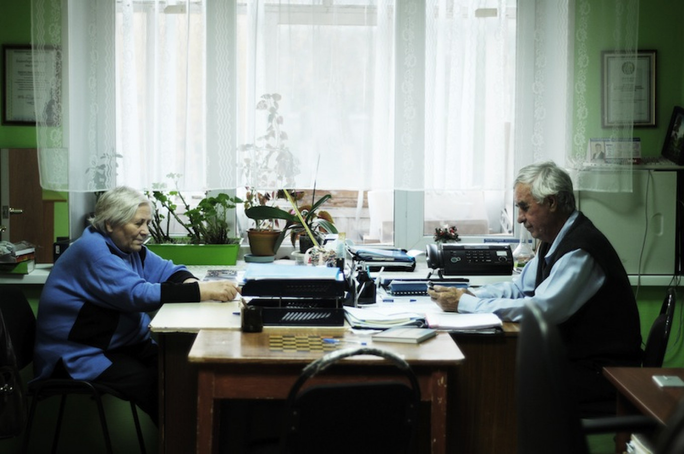 "Pavel Akimov (R) sitting in the small office of the ""Our Memory"" group for the descendants of the kulaks forcibly relocated to Surgut in the 1930s. 				 				Eva Hartog"