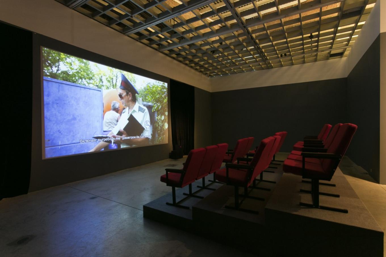 At 'BRAT FILM FEST,' viewers sit in a small movie theater to watch 16 short films by Sergey Bratkov. Regina Gallery