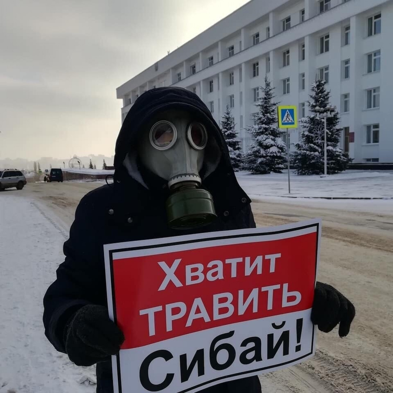 "A local protester raises a poster saying: ""Stop poisoning Sibai!""				 				sibaydishi / Vkontakte"