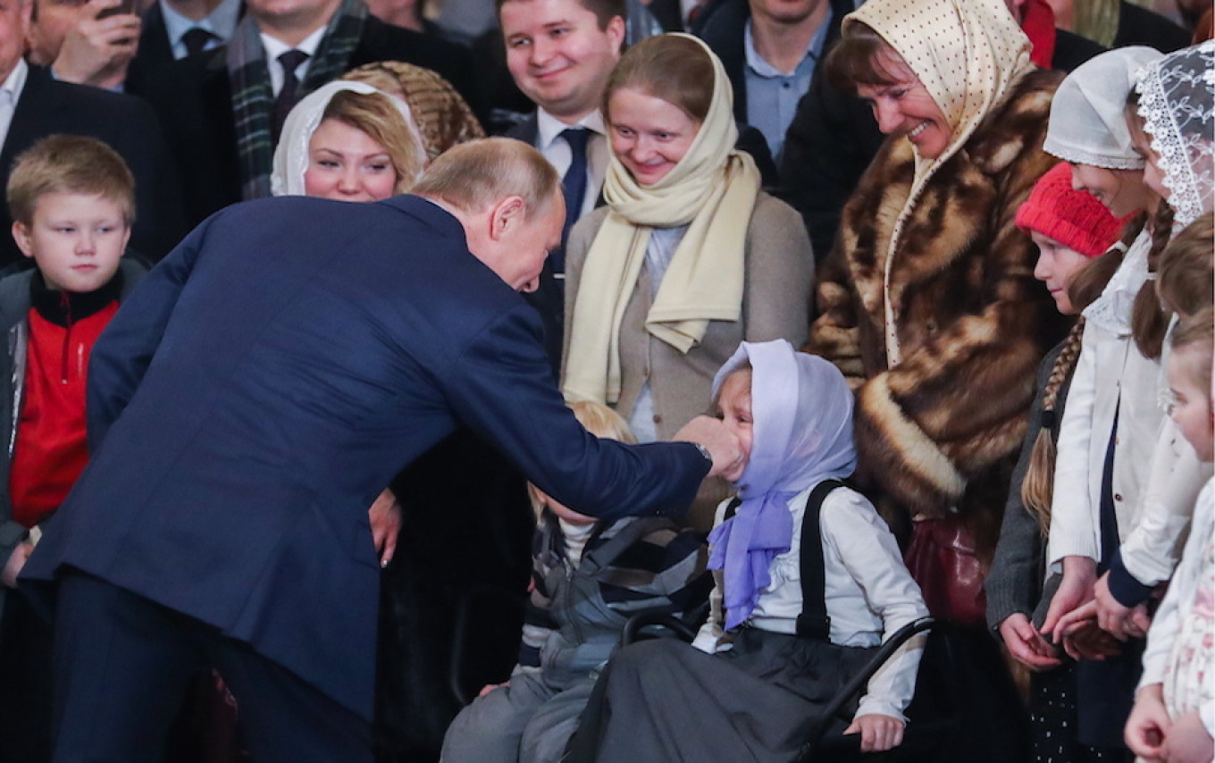 The president shares a moment with a young worshipper in St. Petersburg. 				 				Alexander Demianchuk / TASS